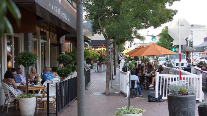 A photo of an outdoor café with sidewalk terrace divided in two parts. The first is next to the building and the second is next to the street.