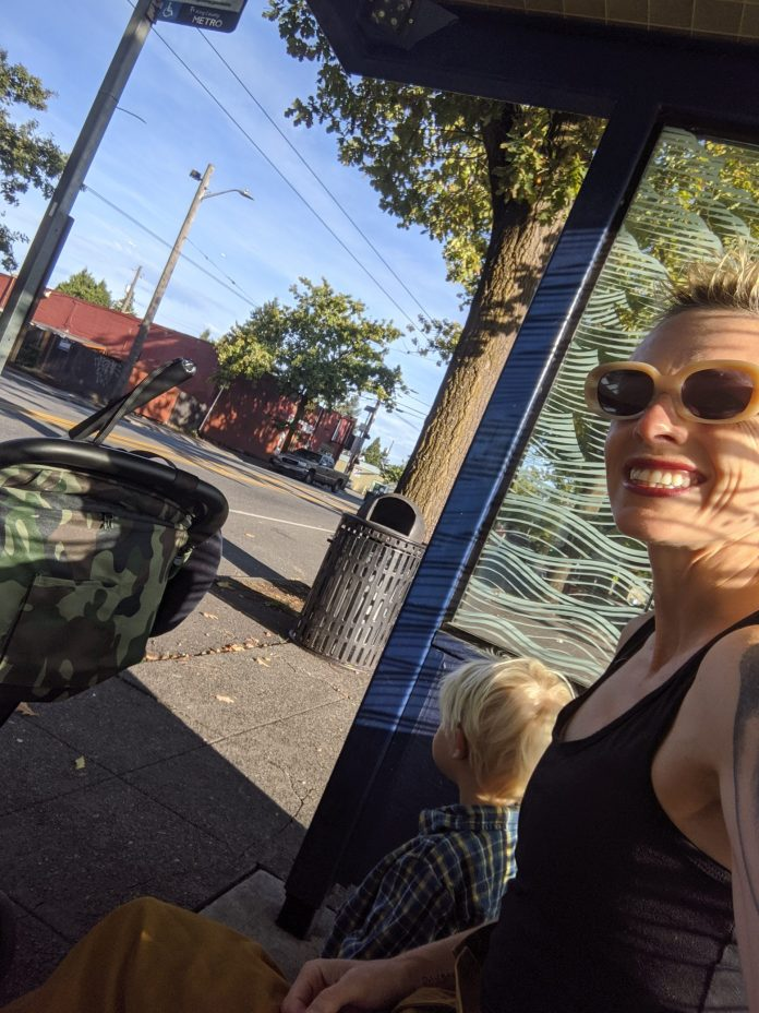 Anna smiles taking a selfie sitting next to her son at a bus stop shelter.