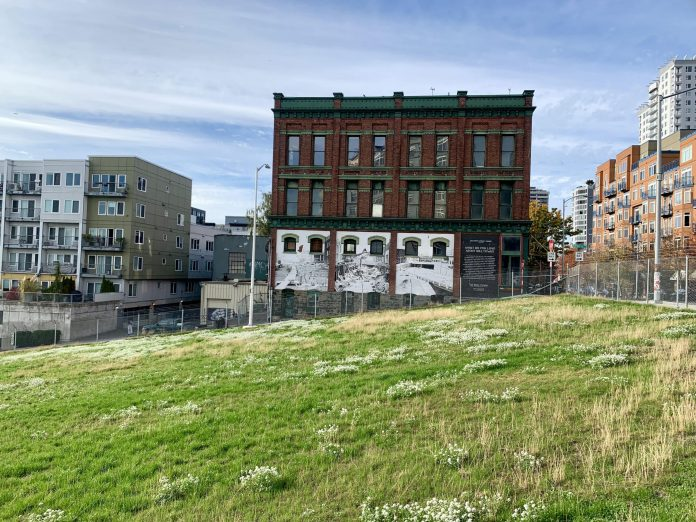 A photo of a green field with a chainlink fence and brick building with a white mural in the background.