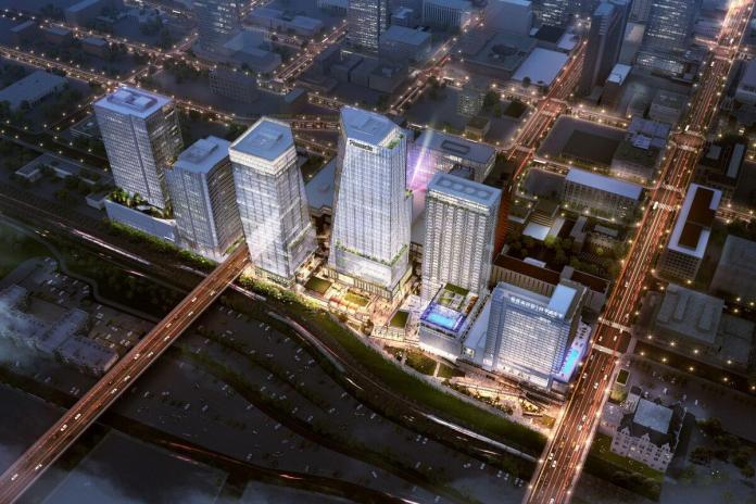 Rendering of five glassy towers, viewed from above, and lit up among a darkened city.