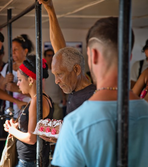 A man carrying home a cake on a bus in Cuba