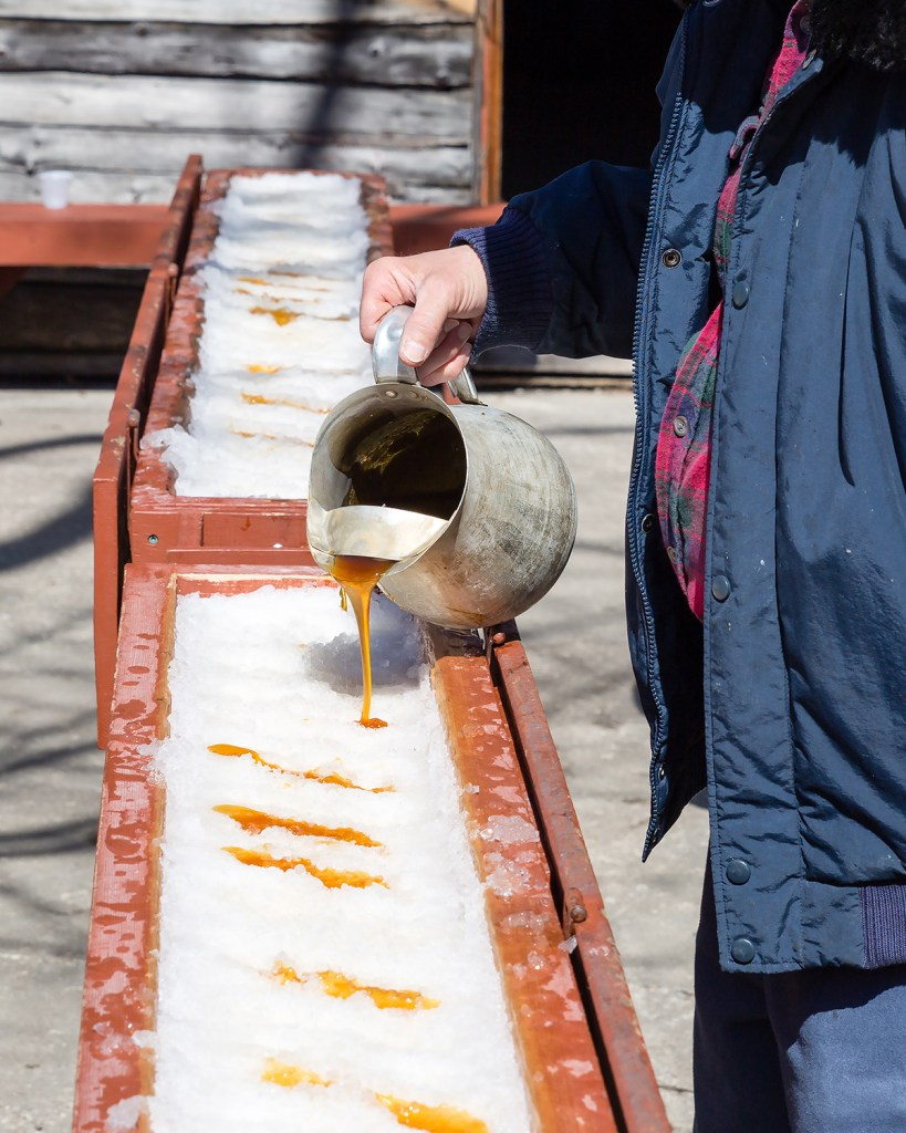Man pouring hot maple syrup on snow (Adobe Stock)
