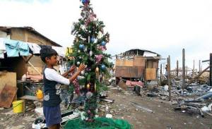 A resident puts the finishing touches on the community Christmas tree - Photo courtesy of George Tapan, Photographer - The Philipine Starweek
