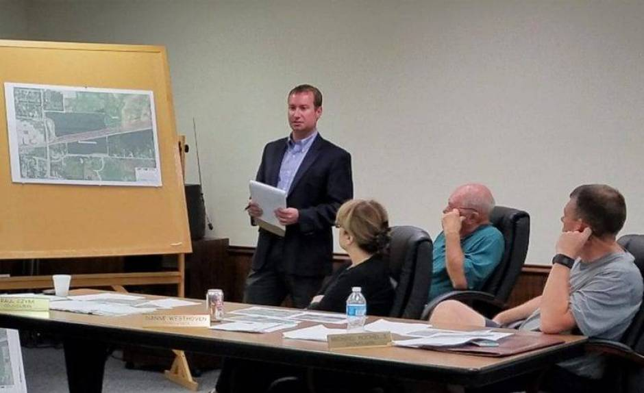 Robert Jones of Norfolk Southern lays out the plans of the new staging yard to the Swanton Village Council as Council Members Diane Westhoven, Paul Dzyak and Mike Rochelle listen.