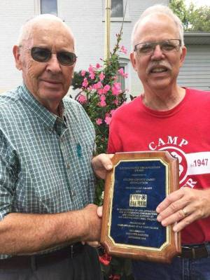 Neree Emmons, President of Fulton County Dairy Association receives a plaque from Bill Goodson in appreciation of their donation to Camp Palmer's pool project.