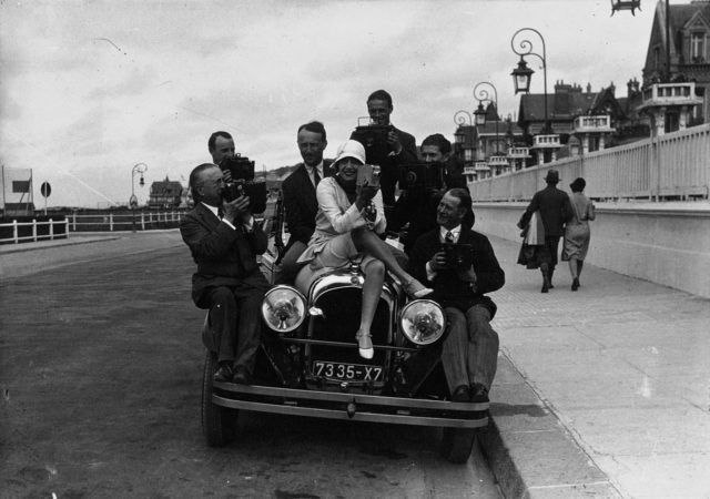 Mistinguett sitting on her Chrysler with a group of photographers in Deauville in 1929. Source
