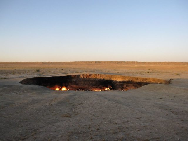 The Soviets were digging for natural gas in 1971, the ground collapsed, and with an explosion was born the Darvaza Gas Crater, burning to this day.Source