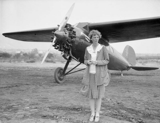 Amelia Earhart at Long Beach, Ca, with her plane. Undated b/w photo.