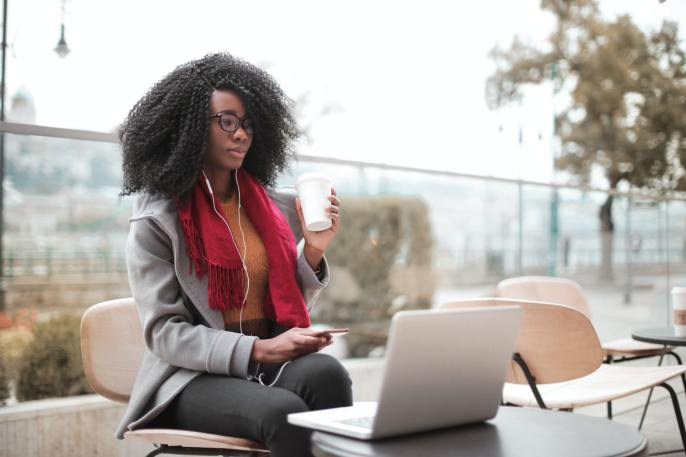 A girl with glasses listening to a website being read, representing the advantages of web accessibility for business websites.