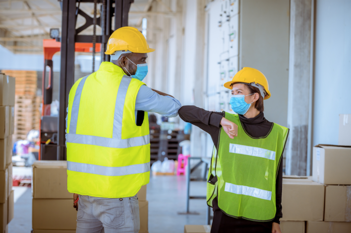 Wearing masks is an important precaution in the workplace. (Photo by: DSCimage | iStock via Getty Images Plus)