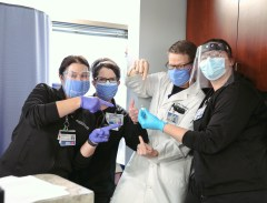"""Leslie Horton (RN), Kimila Brogan (RN), Dr. Ben Heavrin (ED), and Ashley Midkiff point at the Pfizer COVID-19 vaccine (Photo by: Carl """"C-Roy"""" Carswell)"""