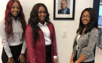 From left, Staff writer Brianna Sparrow, Editor-in-Chief KaBria Kirkham and Staff writer Nyah Peebles stand next to a photo of Deceased Tennessee Reporter and TSU Professor Getahn Ward