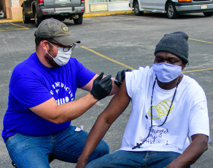 Dr. Pete Cathcart of Neighborhood Health's Street Medicine Team administering COVID-19 vaccine to Deng Autiak in Nashville. (Courtesy Photo)