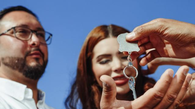 A person giving a house key to buyers