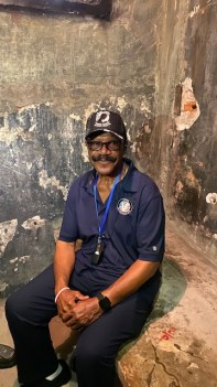 Lt. Col. James Williams sits in cell where he was interrogated and tortured while imprisoned. (Courtesy: Valor Administration)
