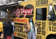 Keosha Thomas standing in front of the Slutty Vegan food truck pop up in Nashville, TN