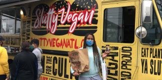 Keosha Thomas standing in front of the Slutty Vegan food truck pop up in Nashville, TN