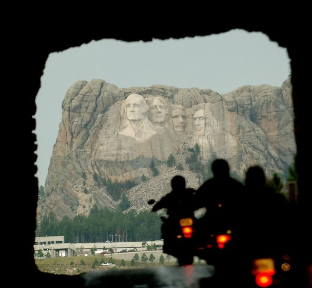 Mt. Rushmore is seen in the distance as a stream of riders passes through a tunnel on Iron Mountain Road in the Black Hills of South Dakota, on Tuesday August 9, 2005.