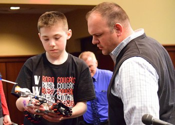 Van Wert Elementary School Robotics Club member Drew Deitemeyer demonstrates how his robot works to Van Wert City Board of Education President R.J. Coleman during Wednesday's school board meeting. (Dave Mosier/Van Wert independent)