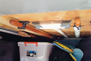 Organize brooms and other supplies by mounting them to the ceiling in outside RV storage closets