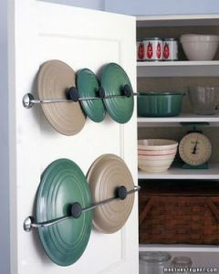 Organize pot lids in camper with curtain rods on the back of cupboard doors