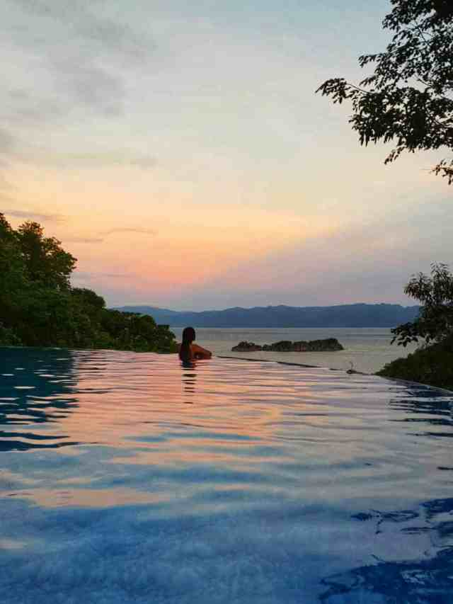 girl enjoying view at sunset from infinity pool at tugawe cove resort in caramoan island in philippines