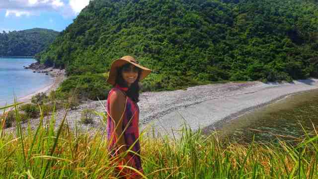 girl hikes to top of Lantangan beach in the caramoan islands on island hopping day tour in philippines
