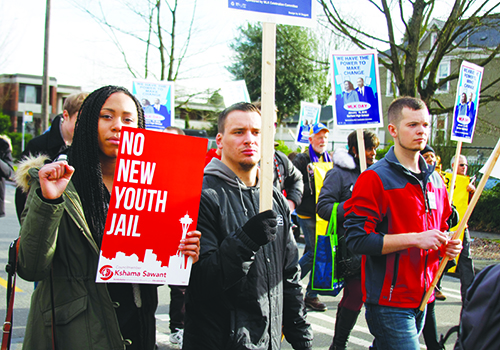 Sasha Lee, Scott McDonald and Evan Bowman hold signs as they march.