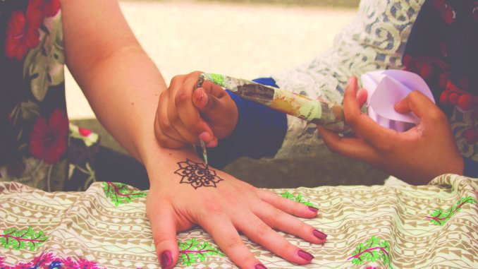 Student receiving a henna tattoo.