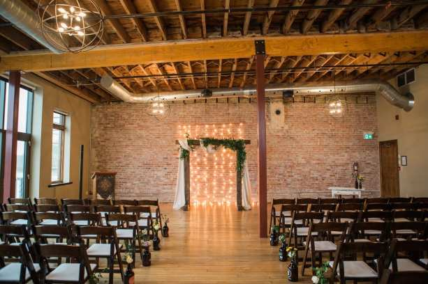 fresh look design wedding ceremony setup with sheer draping, lights and wooden arch