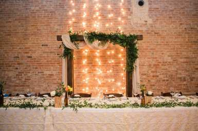 fresh look design wooden arbour with greenery behind wedding head table