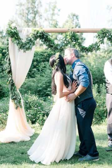 fresh look design bride and groom kissing under a wedding arbour with sheer fabric and greenery