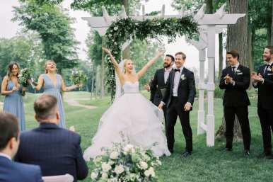 fresh look design wedding ceremony under white wedding arch with greenery
