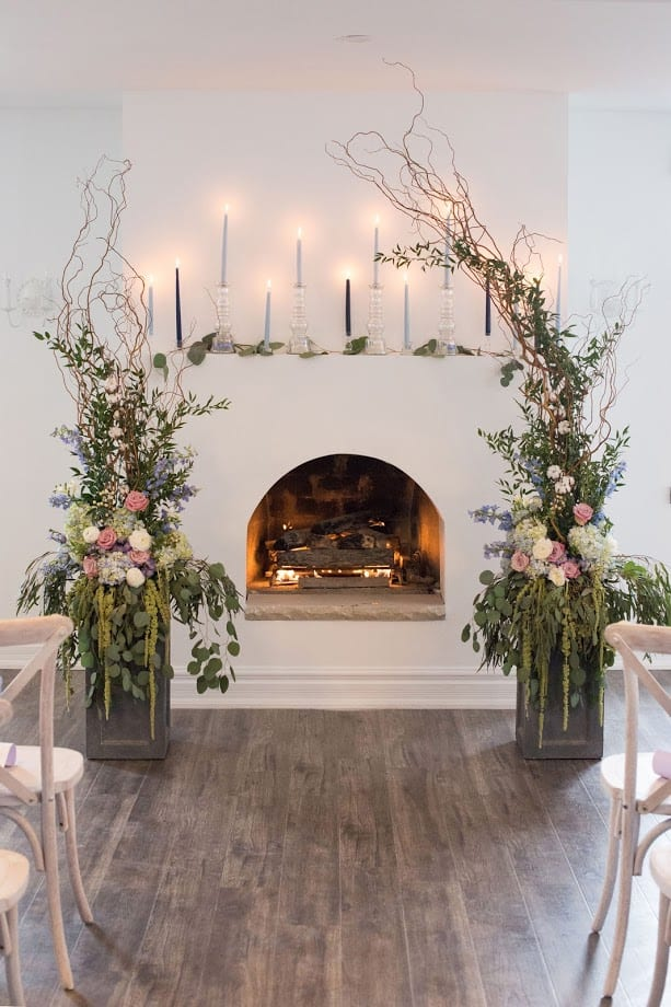 fresh look design greenery and candles in front of a fireplace setup for a wedding ceremony