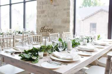 fresh look design long wedding tables in white with greenery and white chivary chairs