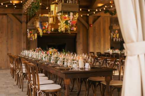 fresh look design long wedding guest tables with hanging florals and candles
