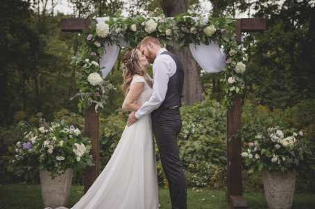 fresh look design bride and groom kissing under a wooden arbour covered in greenery and white flowers