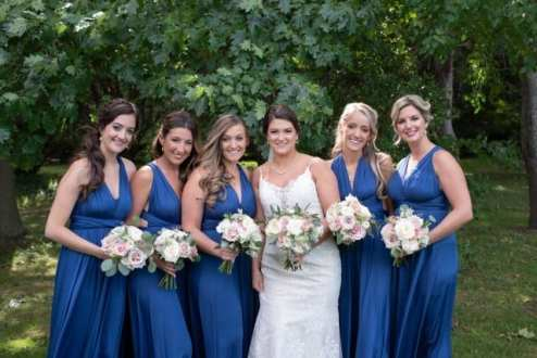 BridesMade bride with her bridesmaids dressed in long blue dresses holding white, pink and green bouquets
