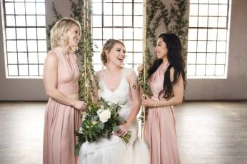 BridesMade bride on a swing with her bridesmaids dressed in long pink gowns/dresses
