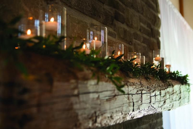 wooden mantle lined with candles and greenery