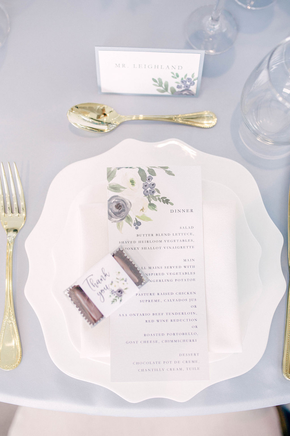 menu card with white and blue flowers with a matching thank you favour box sits on a ornate white plate