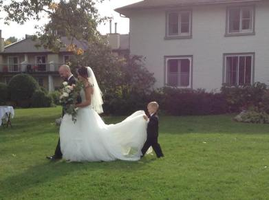 Creme couture bride walking down the aisle with her dad while ring bearer holds her train