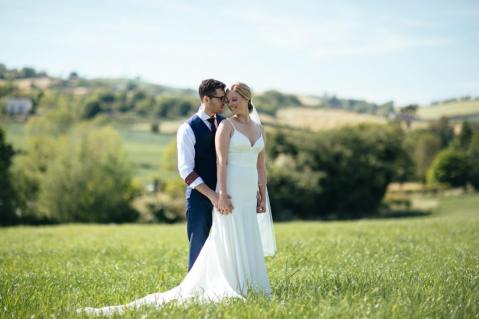 creme couture bride and groom in a field