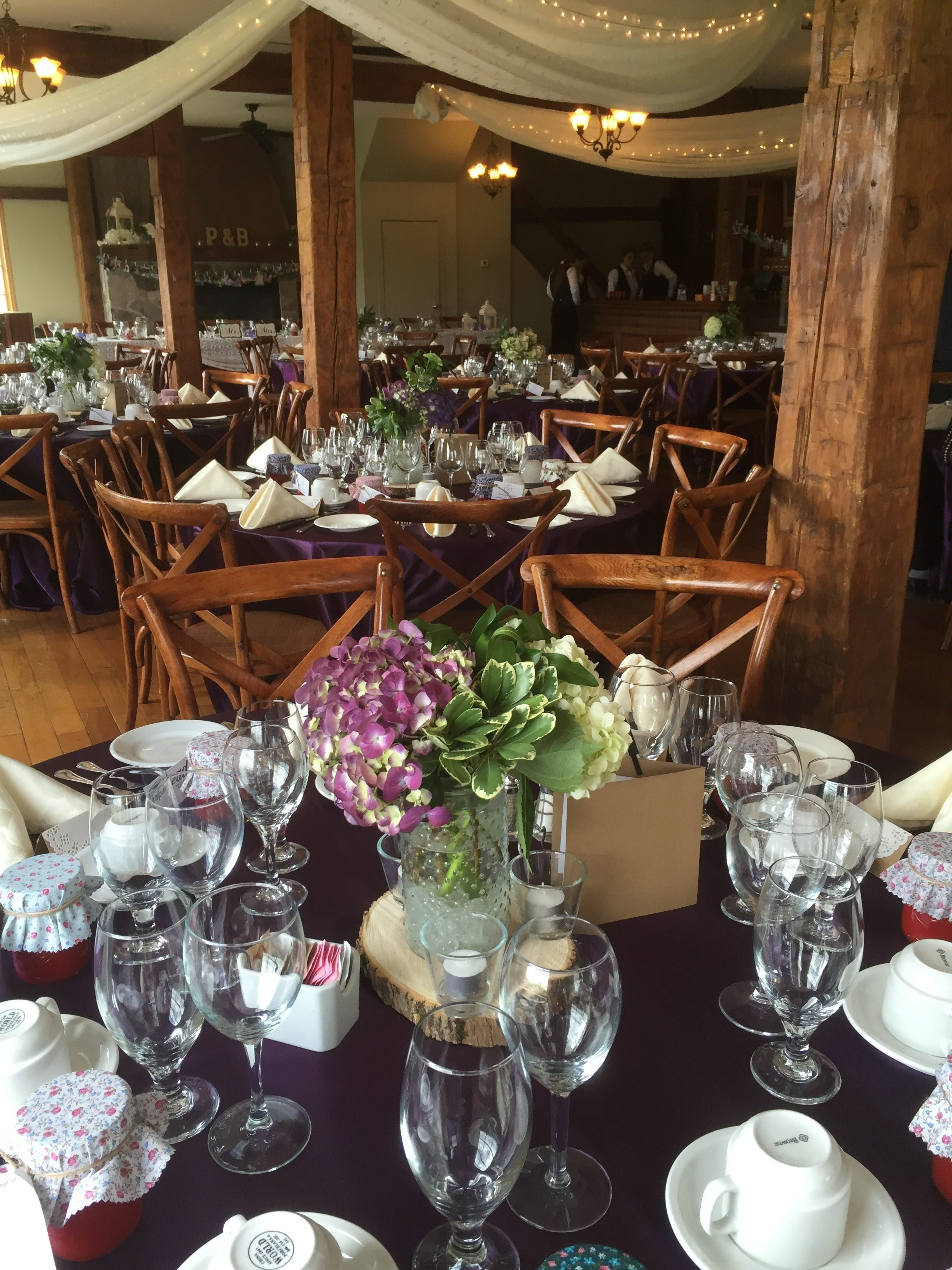 Now & Always purple/black linens and low floral arrangement on wedding guest table
