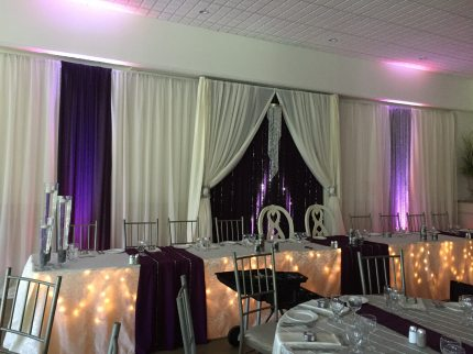 Now & Always purple and white head table back drop with lights