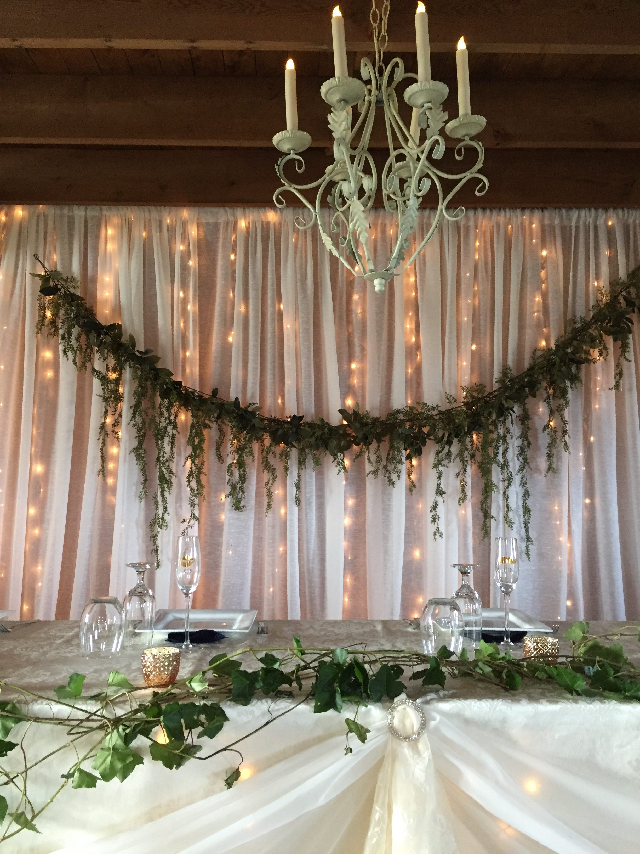 Now & Always white sheer head table backdrop with greenery and lights