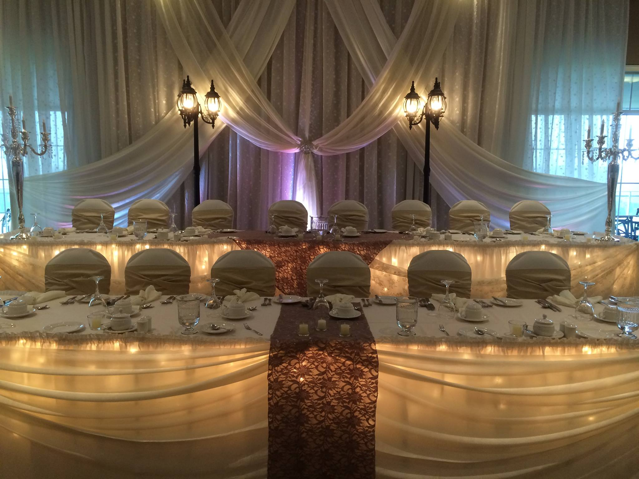 Now & Always white draping backdrop of two tier wedding head table with lampposts and uplighting