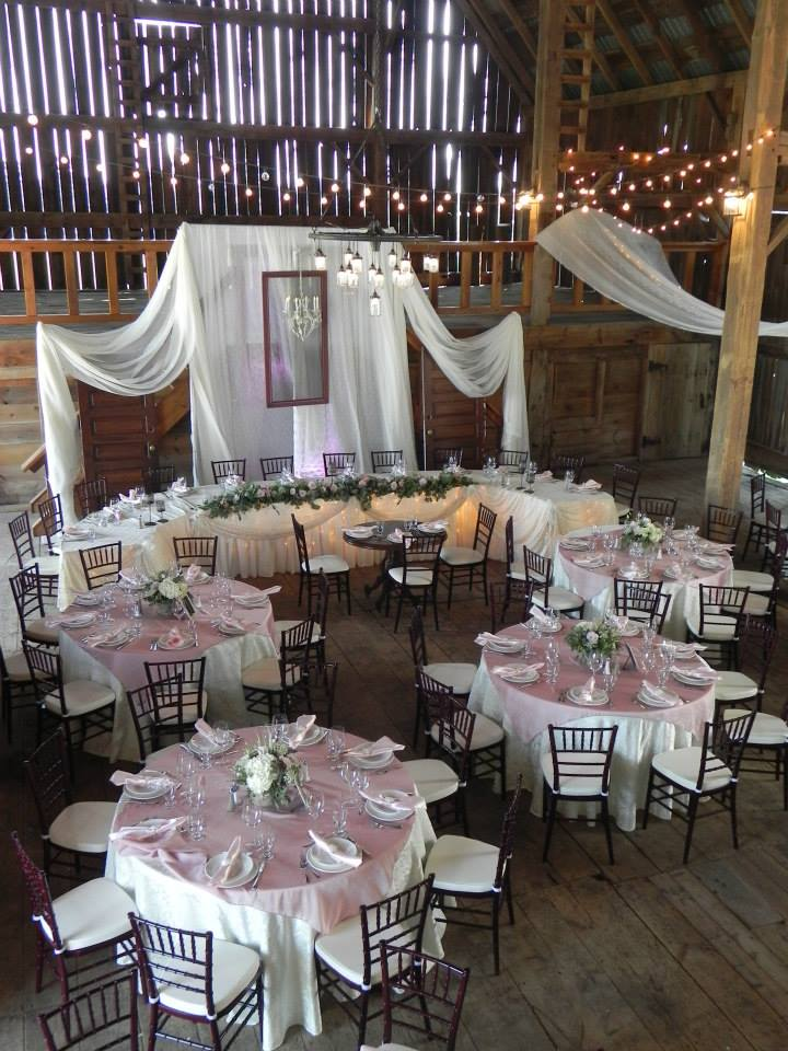 Now & Always barn wedding with white and pink guest tables and white backdrop