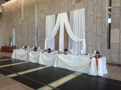 Now & Always long white head table with white draping backdrop on brick wall