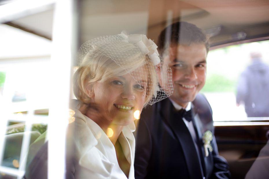 Brautpaar schaut aus dem Hochzeitsauto